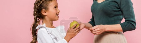 panoramic shot of mother giving tasty apple to cute daughter isolated on pink