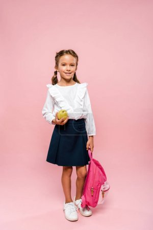 Photo for Happy kid holding tasty and green apple and backpack on pink - Royalty Free Image