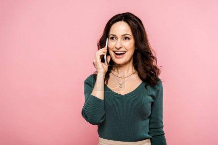 glückliche Frau, die auf dem Smartphone spricht und isoliert auf rosa lächelt