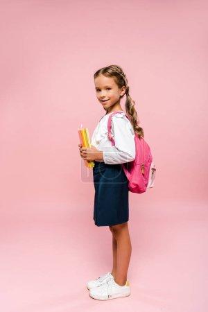 Photo pour Enfant heureux tenant des livres et debout isolé sur rose - image libre de droit