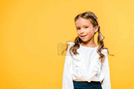 Photo for Happy and cute schoolchild standing isolated on orange - Royalty Free Image