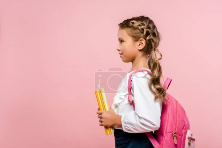 Photo for Side view of happy kid holding books while standing with backpack isolated on pink - Royalty Free Image