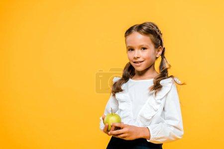 Photo for Happy child holding tasty apple and smiling isolated on orange - Royalty Free Image