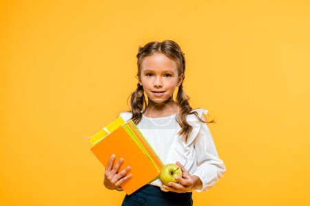 Photo for Happy kid holding books and tasty apple isolated on orange - Royalty Free Image