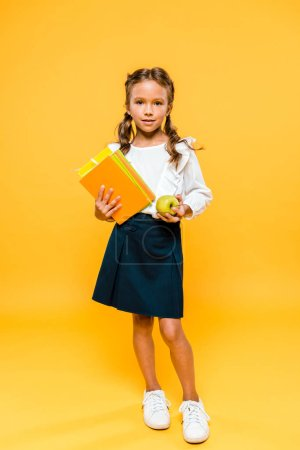 Photo for Happy kid holding books and tasty apple while standing on orange - Royalty Free Image