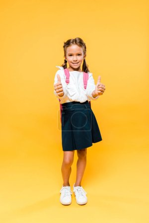 Photo for Happy kid standing and showing thumbs up on orange - Royalty Free Image