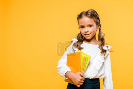 Photo for Smiling and cute kid holding books isolated on orange - Royalty Free Image