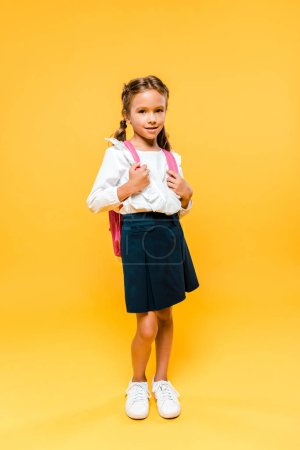 cute schoolkid touching pink backpack while standing on orange
