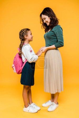 Photo pour Mère heureuse tenant la main avec écolière joyeuse sur orange - image libre de droit