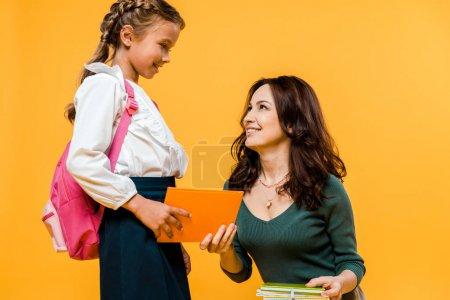 attractive mother giving book to happy schoolgirl isolated on orange