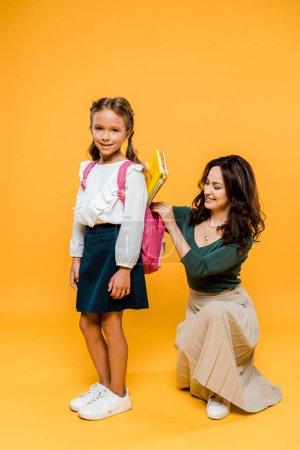 Photo pour Attrayant mère mettre des livres dans le sac à dos de l'écolière sur orange - image libre de droit