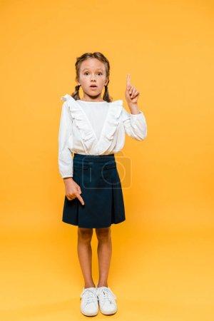 Photo pour Surpris écolier pointant avec les doigts tout en se tenant sur orange - image libre de droit