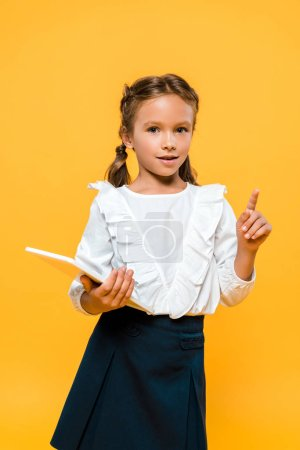 Photo for Happy schoolkid holding book and pointing with finger isolated on orange - Royalty Free Image