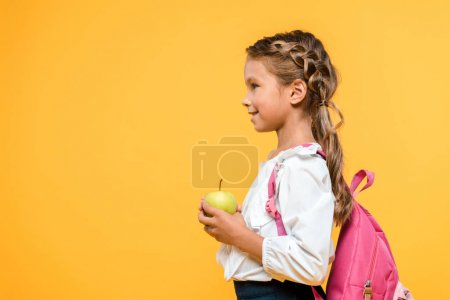 Photo for Side view of happy schoolkid holding apple isolated on orange - Royalty Free Image