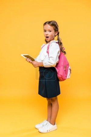 Photo pour Écolier surpris tenant tablette numérique avec écran blanc sur orange - image libre de droit