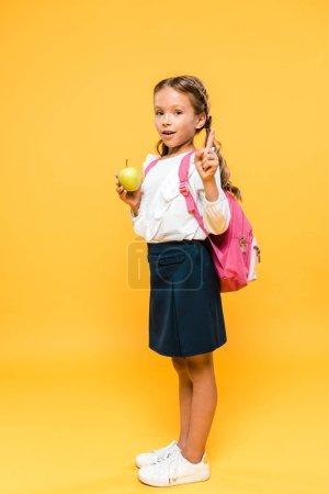 Photo pour Adorable écolier tenant pomme et pointant du doigt sur orange - image libre de droit