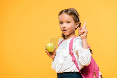 Photo for Adorable schoolkid holding apple and pointing with finger isolated on orange - Royalty Free Image