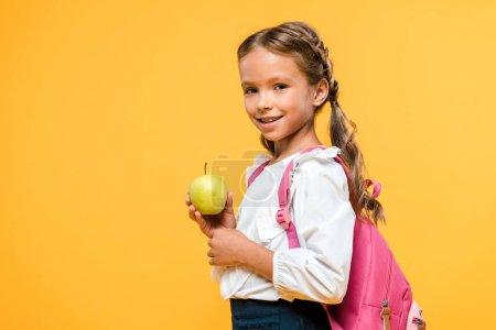 Photo for Happy schoolchild holding tasty apple isolated on orange - Royalty Free Image