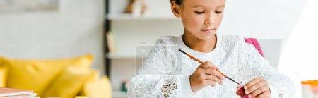 Photo for Panoramic shot of cute kid holding paintbrush near gouache jar - Royalty Free Image