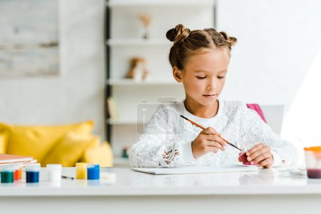 Photo for Cute kid holding paintbrush near gouache jars on table - Royalty Free Image