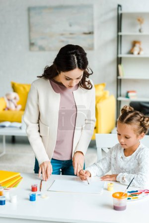 Photo for Attractive mother standing near daughter holding paintbrush near paper - Royalty Free Image