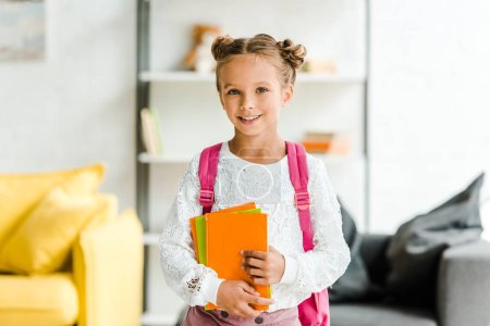 Photo for Happy schoolgirl standing with backpack and holding books - Royalty Free Image