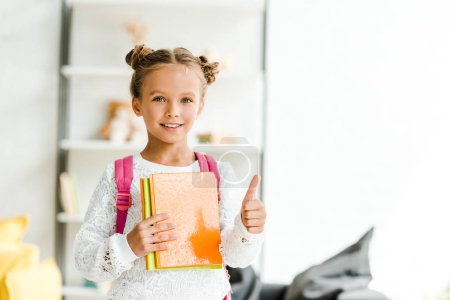 Foto de Happy schoolgirl holding books and showing thumb up at home - Imagen libre de derechos