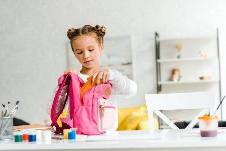 Photo for Cute schoolgirl putting lunch box in pink backpack - Royalty Free Image