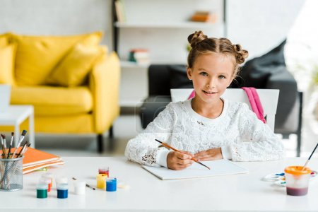 Photo for Happy kid holding paintbrush near gouache jars and paper on table - Royalty Free Image