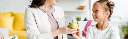 Photo pour Plan panoramique de mère heureuse donnant pomme à fille - image libre de droit