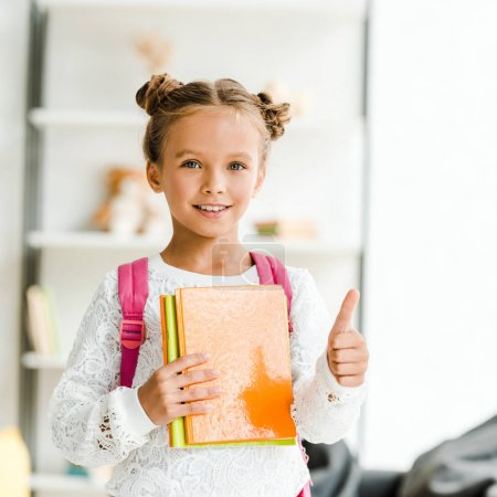 Photo for Cheerful schoolgirl holding books and showing thumb up at home - Royalty Free Image