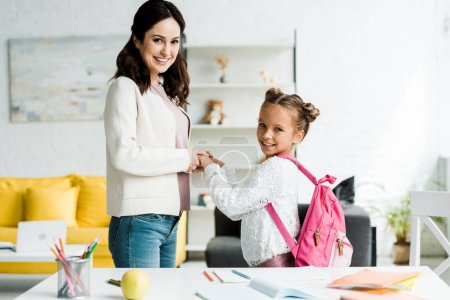 Photo for Happy mother and cheerful and cute daughter holding hands at home - Royalty Free Image