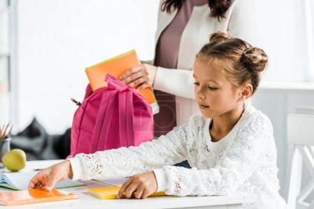 Photo pour Vue recadrée de mère mettant livre dans sac à dos rose - image libre de droit