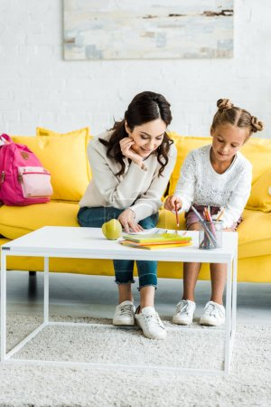 Photo for Happy mother looking at daughter drawing while sitting on sofa - Royalty Free Image