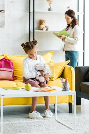Photo for Selective focus of kid holding soft toy while sitting on sofa near mother - Royalty Free Image