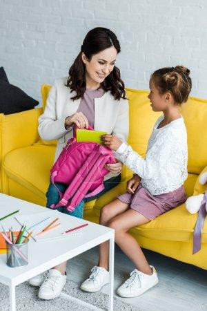Photo pour Mère heureuse mettant le livre dans le sac à dos de l'enfant d'école - image libre de droit