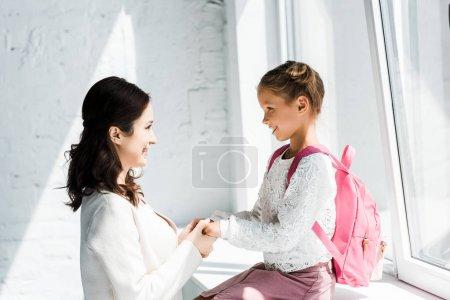 Photo pour Mère heureuse tenant la main avec fille mignonne près des fenêtres - image libre de droit