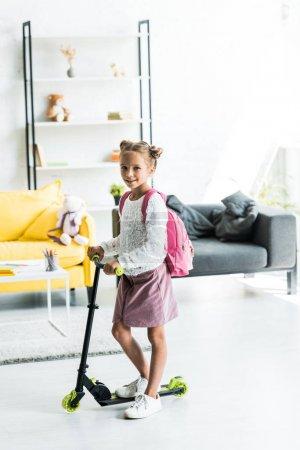Photo pour Heureux enfant debout près de kick scooter à la maison - image libre de droit