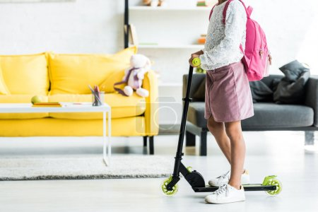 Photo pour Vue recadrée de l'enfant debout près de kick scooter à la maison - image libre de droit