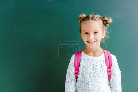 Photo for Happy kid smiling while standing with backpack on green - Royalty Free Image