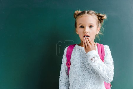 Photo for Surprised schoolgirl covering mouth on green - Royalty Free Image