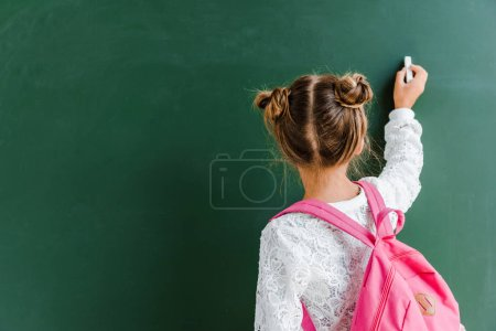Photo for Back view of schoolchild holding chalk near chalkboard on green - Royalty Free Image