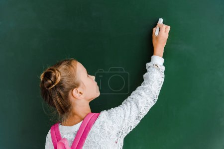 schoolchild holding chalk near chalkboard on green