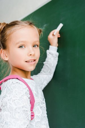 Photo for Selective focus of happy schoolkid holding chalk - Royalty Free Image