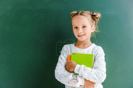 Foto de Smiling schoolgirl smiling while standing with books on green - Imagen libre de derechos