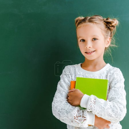Photo for Happy schoolgirl smiling while standing with books on green - Royalty Free Image