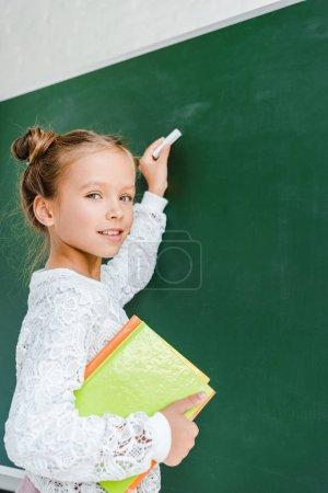 happy schoolkid holding chalk and books near green chalkboard