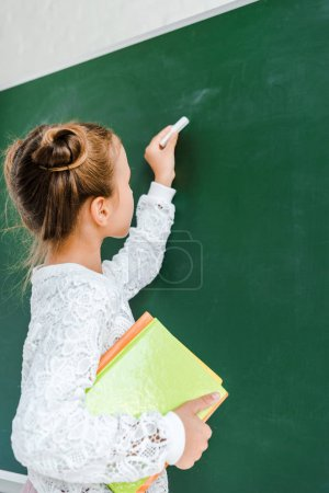 Photo for Cute schoolkid holding chalk and books near green chalkboard - Royalty Free Image