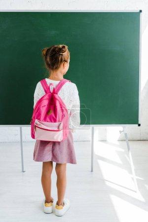 Photo pour Vue arrière de l'écolier debout près du tableau vert dans la salle de classe - image libre de droit