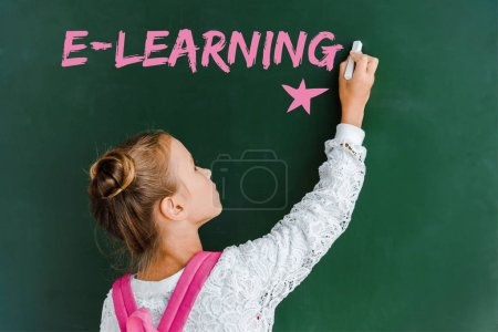 Photo for Schoolchild holding chalk near chalkboard with e-learning lettering on green - Royalty Free Image